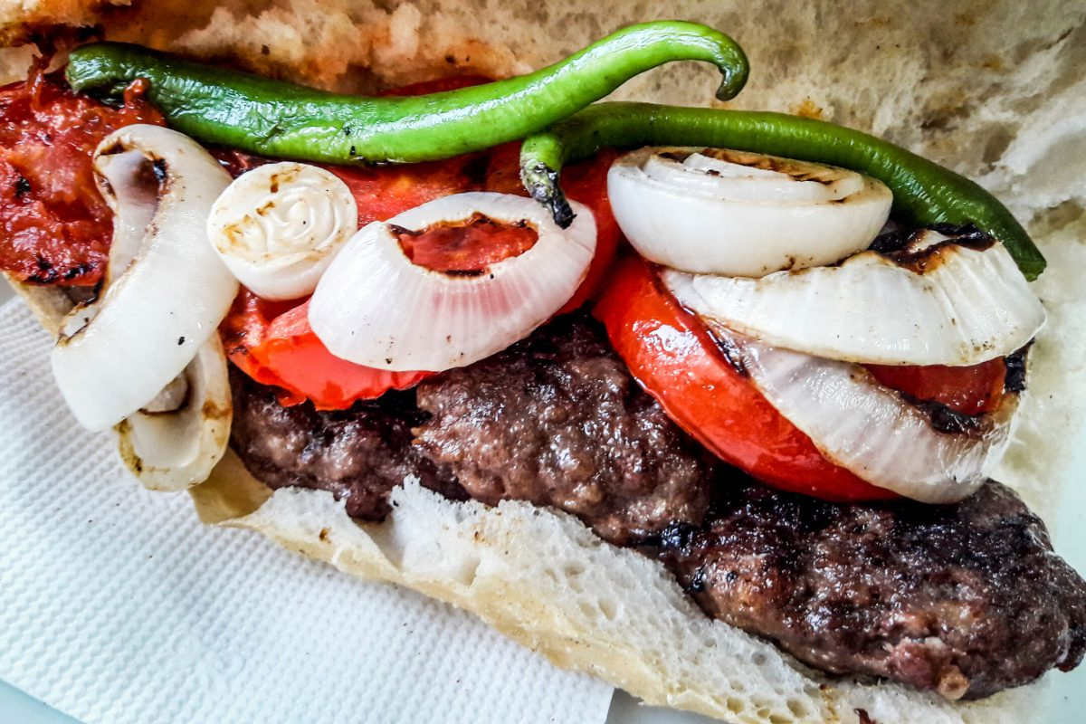 Turkish Kofte Ekmek / Meatball Sandwich with tomatoes, onion and green pepper. Traditional Fast Food.